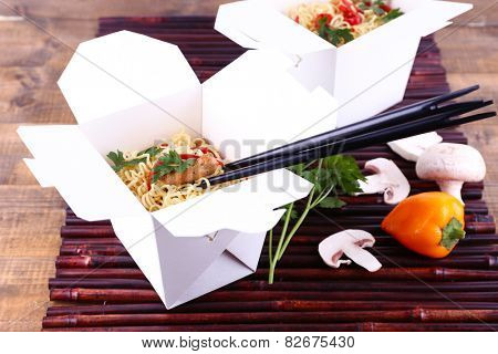 Chinese noodles in takeaway boxes on bamboo mat on wooden background