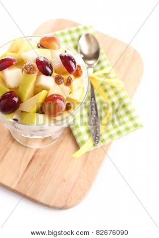 Healthy breakfast - yogurt with  fresh grape and apple slices and muesli served in glass bowl on wooden tray, isolated on white