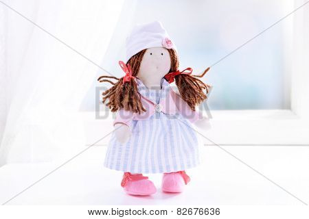 Handmade doll near window close-up