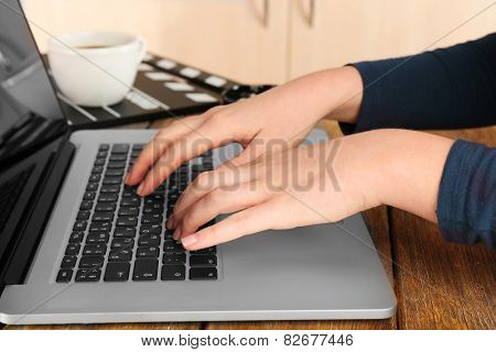 Female hands of scriptwriter working on laptop at desk on cupboard background