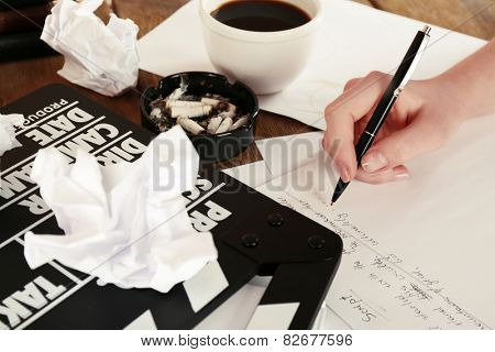 Female hand writing script at desktop with moving clapper and sheets of paper background