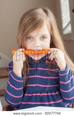 Little Girl Biting On A Carrot