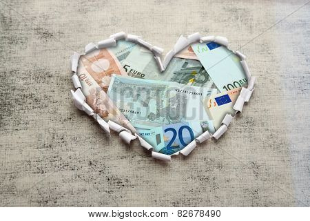 Euro banknotes through torn gray paper