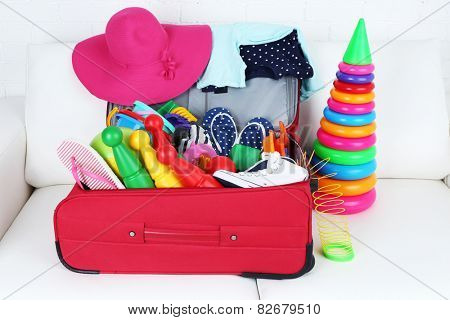 Suitcase packed with clothes and child toys on white sofa and brick wall background