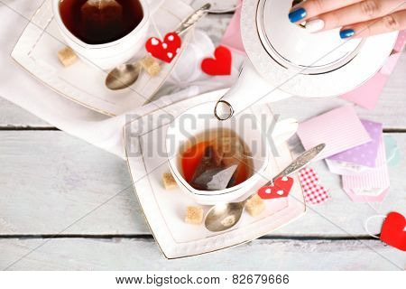 Woman pouring hot tea from teapot into cup wooden background