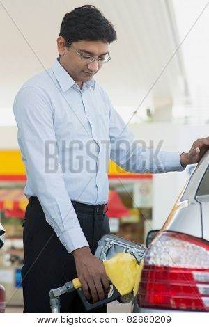 Pumping gas. Asian Indian man pumping gasoline fuel in car at gas station.