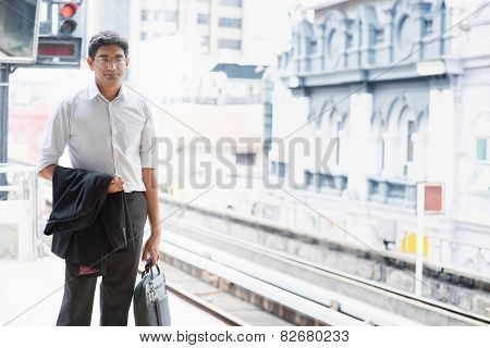 Asian Indian business people waiting train at railway station.