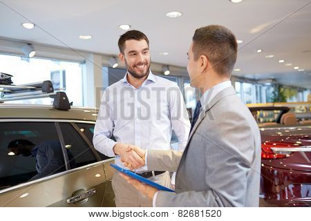 auto business, car sale, technology, gesture and people concept - happy man and car dealer with tablet pc computer shaking hands in auto show or salon