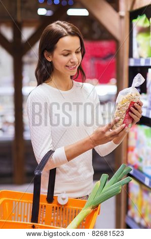 sale, shopping, consumerism and people concept - happy young woman with food basket choosing muesli in market