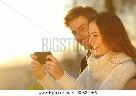 Couple Watching Media Videos In A Smart Phone