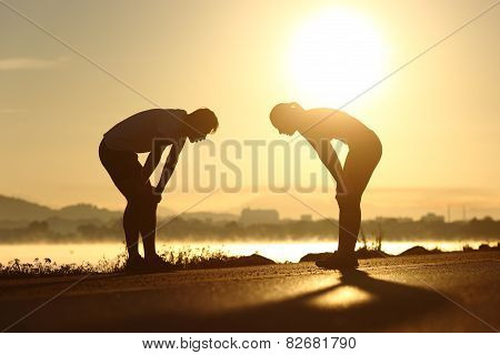 Exhausted And Tired Fitness Couple Silhouettes At Sunset
