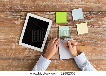 business, education, people and technology concept - close up of female hands with tablet pc computer and stickers writing to notebook on table