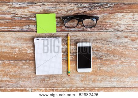 business, education and technology concept - close up of smartphone, paper stickers, pencil and eyeglasses on table in office