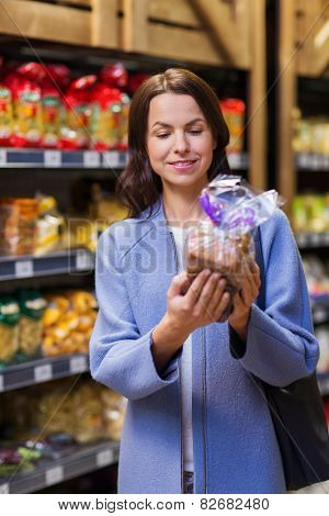 sale, shopping, consumerism and people concept - happy young woman choosing and buying bread in market