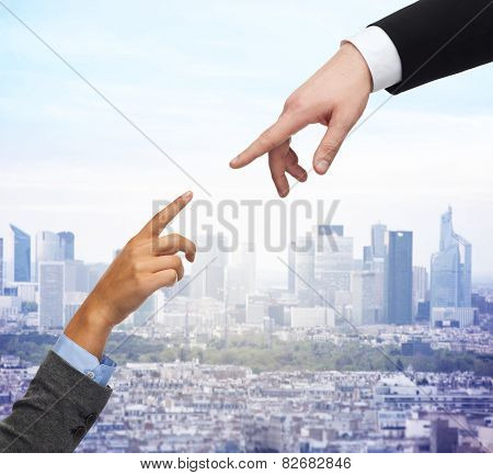 business, people and connection concept - close up of woman and man hands trying to connect over city background