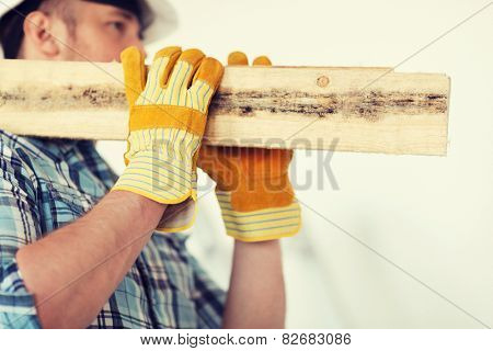 repair, building and home concept - close up of male in gloves and helmet carrying wooden boards on shoulder