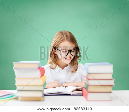 education, people, children and school concept - happy student girl in eyeglasses reading book over green chalk board background