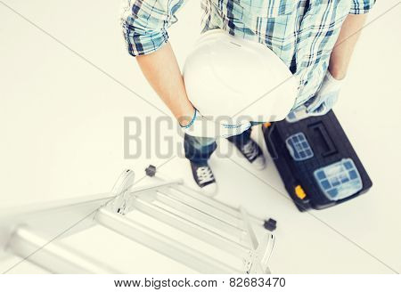 architect and home renovation concept - man with ladder, helmet and toolkit