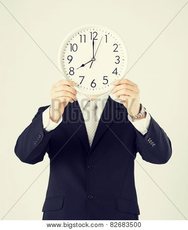 man covering his face with wall clock.