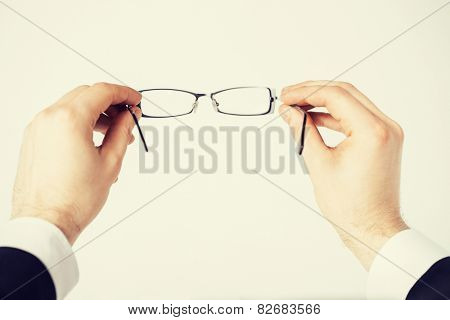 close up of man hands holding eyeglasses