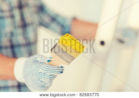 repair, building and home concept - close up of male in gloves holding paintbrush
