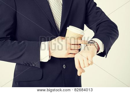 close up of man with take away coffee looking at wristwatch