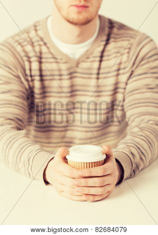 close up of man hand holding take away coffee cup