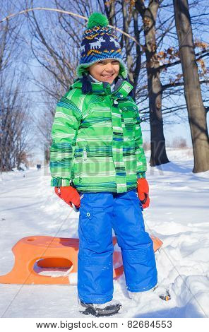 Little boy having fun with sled in winter park
