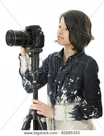 An attractive young teen patiently waiting for the right moment before clicking her tripod held camera for a great shot.   On a white background.