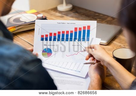 Closeup of businessman and woman discussing on stockmarket document in office