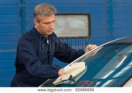 Portrait Of A Mature Mechanic Cleaning Windshield With A Cloth At Garage