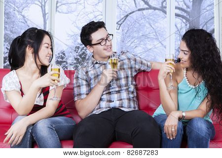 Multiracial Teenager Drinking Beer On Sofa