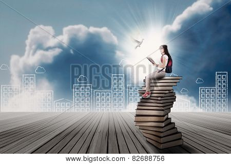 Student Sitting On A Stack Of Book