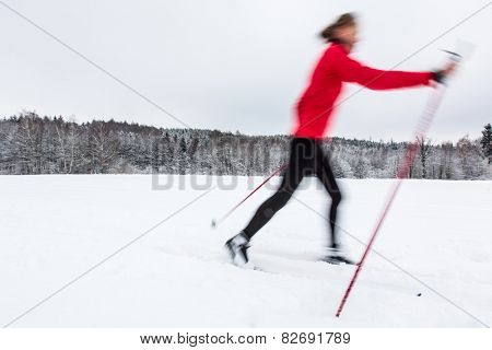 Cross-country skiing: young woman cross-country skiing on a winter day (motion blurred image)
