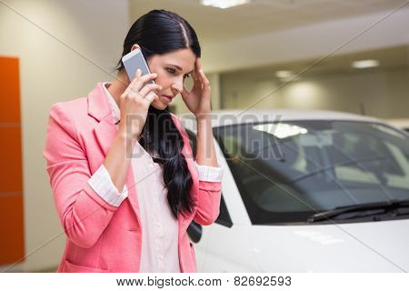 Sad woman calling someone with her mobile phone at new car showroom