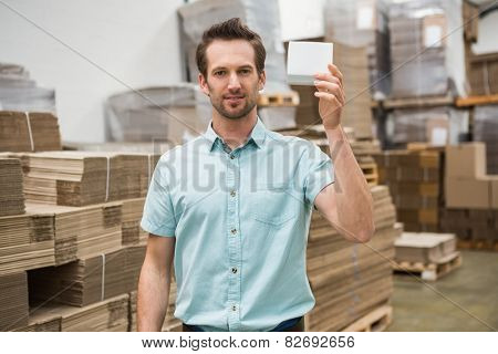 Smiling warehouse worker showing a small box in a large warehouse