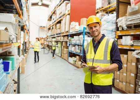 Warehouse worker smiling at camera with clipboard in a large warehouse