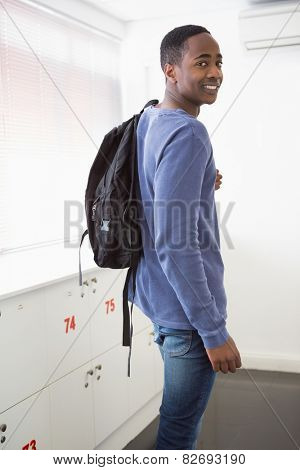 Smiling university student with backpack at the university