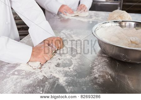 Close up of bakers kneading dough at counter in the kitchen of the bakery