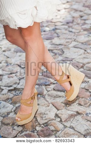 Womens legs in wedge heels on a sunny day in the city