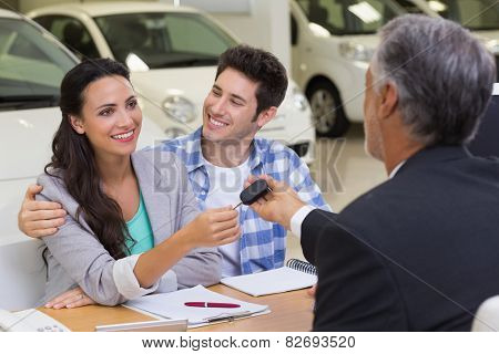 Salesman giving car keys to a couple at new car showroom