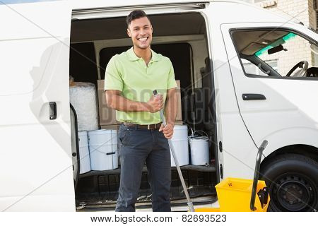 Cleaning agent standing smiling at camera in front of his van