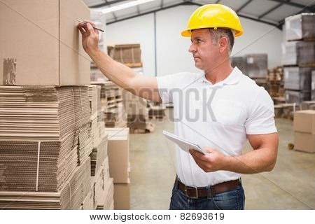 Warehouse worker writing on a box in a large warehouse