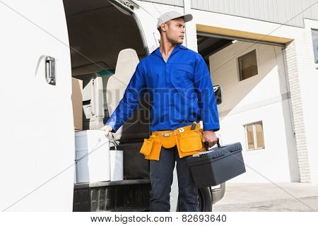 Serious handsome handyman holding toolbox in front of his van