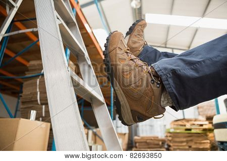 Low section of worker falling off ladder in the warehouse