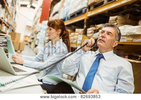 Manager working on laptop and talking on phone at desk in a large warehouse