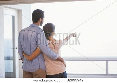 Cute couple looking out the window in their new home