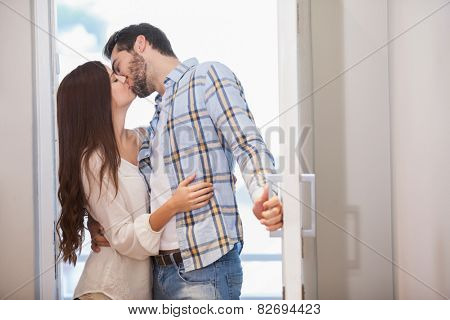 Young couple kiss as they open front door in their new home