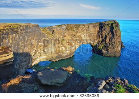 The cape Dirkholaey in the south of Iceland. The enormous rock elephant it is lit with a summer. The sunset in July