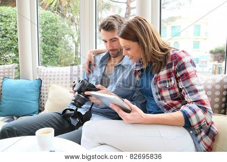 Couple sitting in coffee shop watching photos